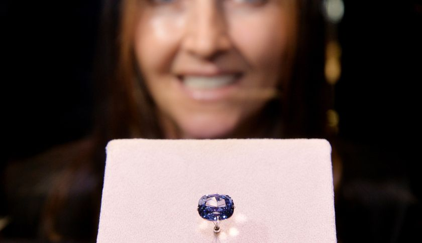 """Suzette Gomes, CEO of Cora International, poses with the 12-carat """"Blue Moon Diamond"""" which is on display at the Natural History Museum in Los Angeles on September 12, 2014. The 'Fancy Vivid Blue Diamond' which are extremely rare was discovered in South Africa. AFP PHOTO/Mark RALSTON (Photo credit should read MARK RALSTON/AFP/Getty Images)"""